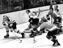 Seals vs Flyers, Gary Croteau chasing puck, Flyers Wayne Hillman, Larry Hale and Frank Spring. (1971 photo/Ron Riesterer)